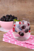 Cold cocktail with forest berries, frozen in ice cubes and fresh blackberry in bowl on color wooden background — Foto Stock