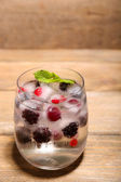 Cold cocktail with forest berries, frozen in ice cubes on wooden background — Stock Photo