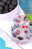 Cold cocktail with forest berries, frozen in ice cubes and fresh blackberry in bowl on color wooden background — Stok fotoğraf