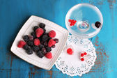 Frozen forest berries on plate and cocktail with berries, frozen in ice cubes on wooden table background — Foto Stock