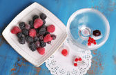Frozen forest berries on plate and cocktail with berries, frozen in ice cubes on wooden table background — Stok fotoğraf