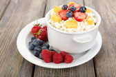 Cottage cheese with fruits and berries in bowl on wooden table   — Stock Photo