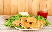 Bolachas de sanduíche com queijo e tomate suco na toalha de mesa com fundo de madeira — Fotografia Stock