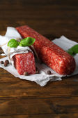 Tasty salami sausage and spices on wooden background — Stock Photo