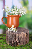 Beautiful lilies of the valley in jar on stump, on nature background — Zdjęcie stockowe