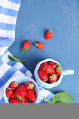Ripe sweet strawberries in mugs  on color wooden background — Stock Photo