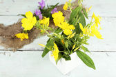 Beautiful yellow wild flowers in vase on color wooden background — Stock Photo