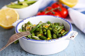 Salad with green beans and corn, and sauce on plate, on color wooden background — Stock Photo