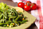 Salad with green beans and corn, sesame seeds on plate, on color wooden background — Stock Photo