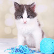 Cute little kitten playing with thread ball on light background — Stock Photo #51170451