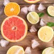 Different sliced juicy citrus fruits with ice on wooden table — Stock Photo #51173575