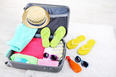 Suitcase with things on white carpet on the floor for travelling somewhere close to water for spending summer vacation — Stock Photo