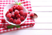 Ripe sweet raspberries in bowl on table close-up — Stockfoto