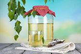 Glass and large flagon of fresh birch sap  on a wooden table on nature background — Stock Photo