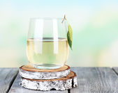 Glass of fresh birch sap on a wooden table on nature background — Stock Photo