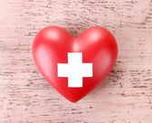 Red heart with cross sign on color wooden background — Stock Photo