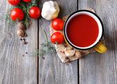 Hausgemachte tomatensaft in farbe becher, gewürzen und frischen tomaten auf hölzernen hintergrund — Stockfoto