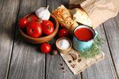 Hausgemachte tomatensaft in farbe becher, brot-sticks, gewürzen und frischen tomaten auf hölzernen hintergrund — Stockfoto
