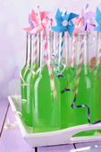 Bottles of drink with straw on table on bright background — Stockfoto
