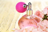 Perfume bottle with petals on table close-up — Stock Photo