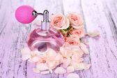 Perfume bottle with petals on table close-up — Stockfoto