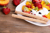 Fresh fruits salad with ice cream on plate and berries on wooden background — Stock Photo