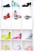 Colorful female shoes on wooden shelves — Stock Photo