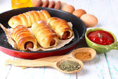 Baked sausage rolls in pan on table close-up — Stock Photo