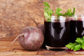 Glasses of fresh beet juice and vegetables on wooden background — Stock Photo