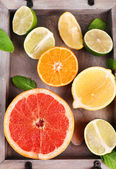 Different sliced juicy citrus fruits on wooden tray — Stock Photo