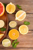 Different sliced juicy citrus fruits on wooden table — Stock Photo
