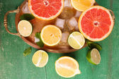 Different sliced juicy citrus fruits with ice on tray, on green wooden table — Foto de Stock