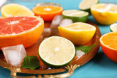 Different sliced juicy citrus fruits with ice on tray, on blue wooden table — Stock fotografie
