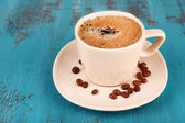 Cup of coffee on color wooden background — Stock Photo