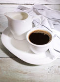Cup of coffee, creamer on color wooden background — Stock Photo