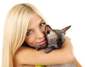 Beautiful young woman holding gray sphinx cat isolated on white — Stock Photo