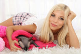 Beautiful young woman with gray sphinx cat lying on plaid in room — Stock Photo