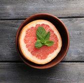 Part of ripe grapefruit in bowl — Stock Photo
