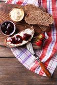 Ahşap arka plan üzerinde ev yapımı tereyağı ve çilek reçel taze tost — Stok fotoğraf