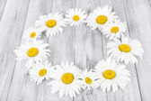 Chamomile wreath on wooden background — Stock Photo