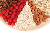 Big round plate with raisins, raspberries, oatmeal, nuts and dried apricots divided on sectors on white background isolated — Stock Photo