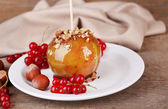 Sweet caramel apple on stick — Stock Photo