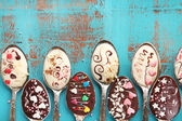 Spoons with tasty chocolate for party on old blue wooden table — Stock Photo