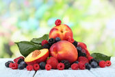 Peaches with berries on table on natural background — Stock Photo
