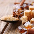 Brown sugar cubes, reed and crystal sugar, spices on wooden background — Stock Photo #51241727