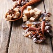 Brown sugar cubes, reed and crystal sugar, spices on wooden background — Stock Photo #51241769