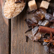 Brown sugar cubes, reed and crystal sugar, spices on wooden background — Stock Photo #51241839