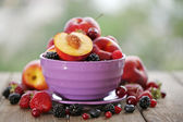Peaches and berries in bowl — Stock Photo