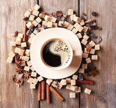 Brown sugar, spices and cup of coffee on wooden background — Stockfoto