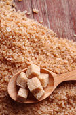 Brown sugar cubes in wooden spoon on crystal sugar background — Stockfoto